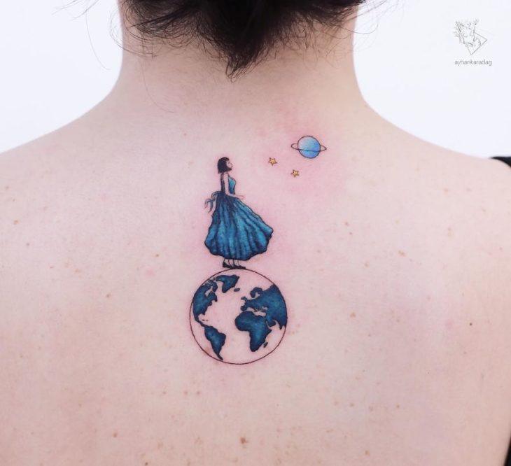 Tatuaje de una chica parada sobre un mundo mientras admira a otro planeta