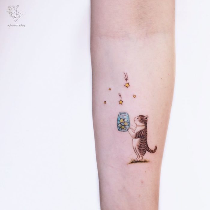 Tatuaje de un pequeño gato soltando mariposas de un frasco