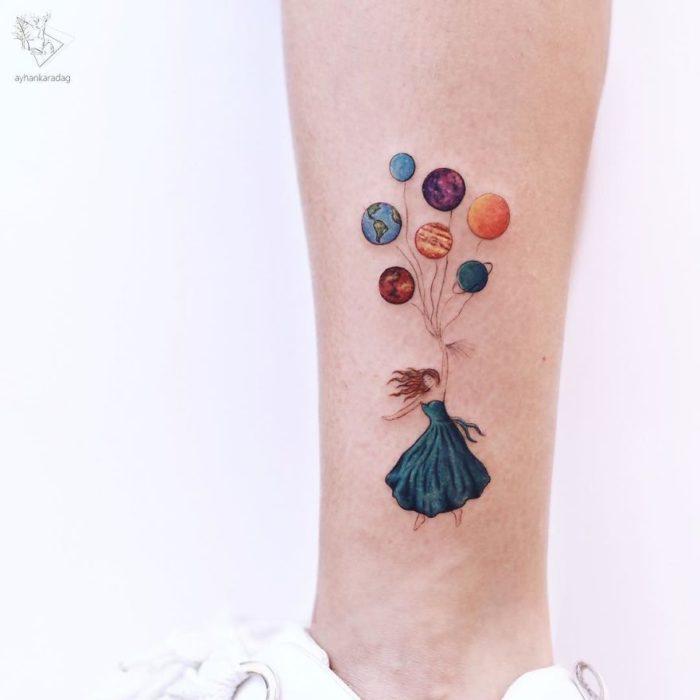 Tatuaje de una chica sujetando unos globos mientras vuela