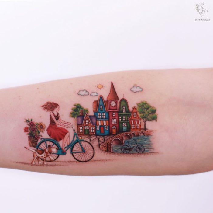Tatuaje de una chica que recorre un pueblo en bicicleta