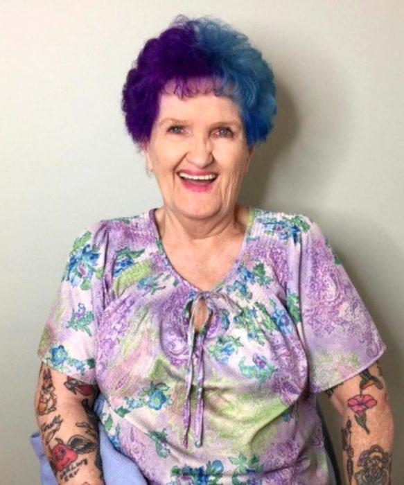 Abuelas con cabellera de colores; viejita con cabello de dos tonos, morado y azul, con tatuajes en losa brazos