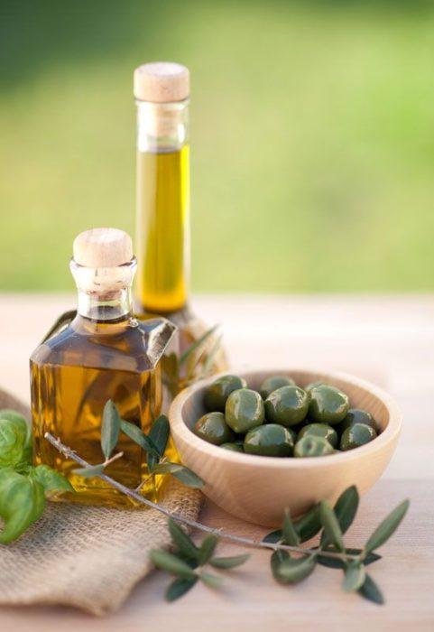 Aceite de oliva en botella de cristal y hojas de olivo