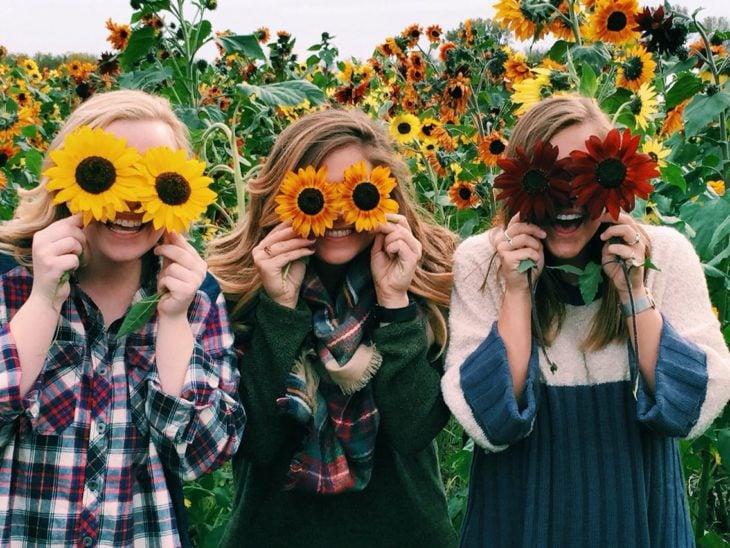Amigas con flores en el rostro y felices
