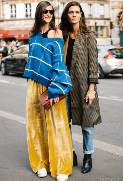 Looks con baggy jeans; amigas en la calle con suéter oversized azul, pantalón holgado amarillo de gamuza, saco largo café