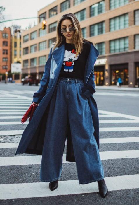 Looks con baggy jeans; mujer posando en cruce en la calle, con gabardina de mezclilla, pantalón oversized y playera de Hello Kitty
