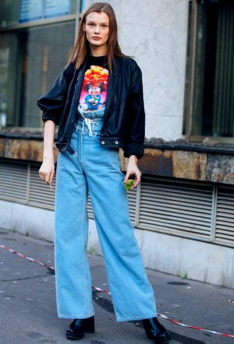 Looks con baggy jeans; mujer con chamarra de cuero negro, pantalón azul de mezclilla oversized