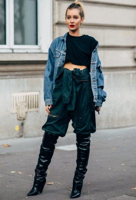 Looks con baggy jeans; mujer con chamarra de mezclilla oversized, pantalones de gabardina verdes holgado, con botas largas a la rodilla