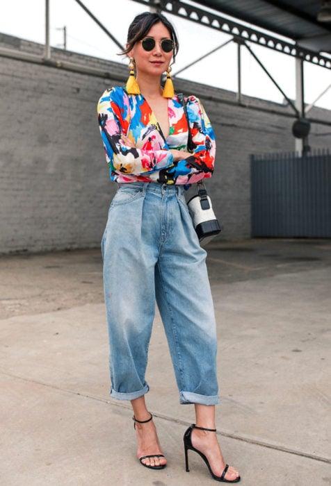 Looks con baggy jeans; mujer de lentes oscuros, aretes amarillos, blusa de colores, pantalones oversized y sandalias de tacón