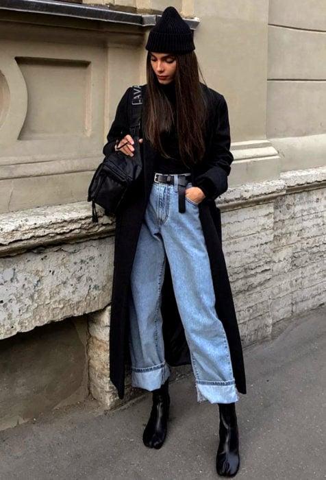 Looks con baggy jeans; chica con gorro, abrigo negro, botines y pantalón de mezclilla oversized