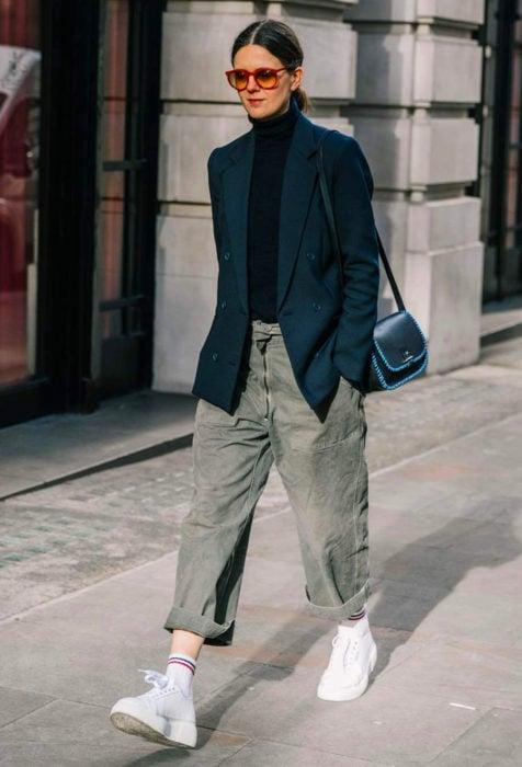 Looks con baggy jeans; mujer caminando en la calle con lentes rojos para el sol, sacp de vestid, pantalones oversized y tenis blancos
