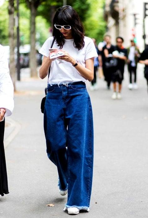 Looks con baggy jeans; mujer caminando en la calle mirando su celular, con blusa blanca básica y pantalones holgados