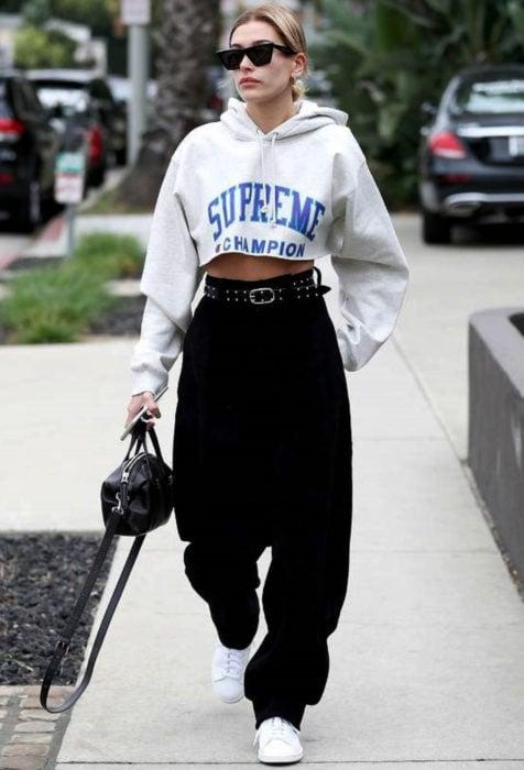 Looks con baggy jeans; Hailey Bieber caminando en la calle con hoodie crop top oversized, pantalones negros holgados con cinto de estoperoles y bolsa de mano
