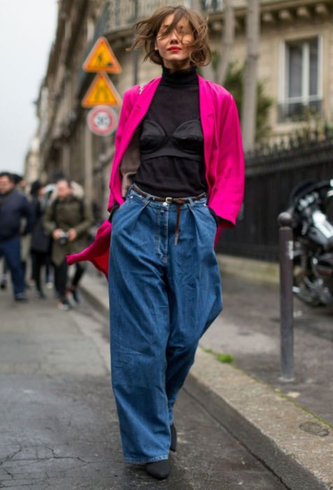 Looks con baggy jeans; mujer con look alocado, saco rosa fuscia, blusa de cuello de tortuga, pantalón oversized, chica caminando en la calle con la manos metidas en las bolsas
