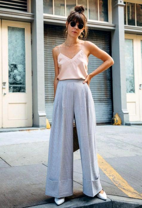 Looks con baggy jeans; mujer con peinado de chongo alto y fleco, con pantalones oversized y blusa de tirantes, lentes oscuros