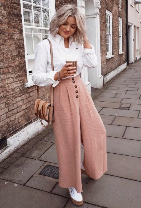Looks con baggy jeans; mujer de cabello rubio, corto y ondulado, con pantalones holgados color rosa salmón, blusa blanca de vestir y bolsa café