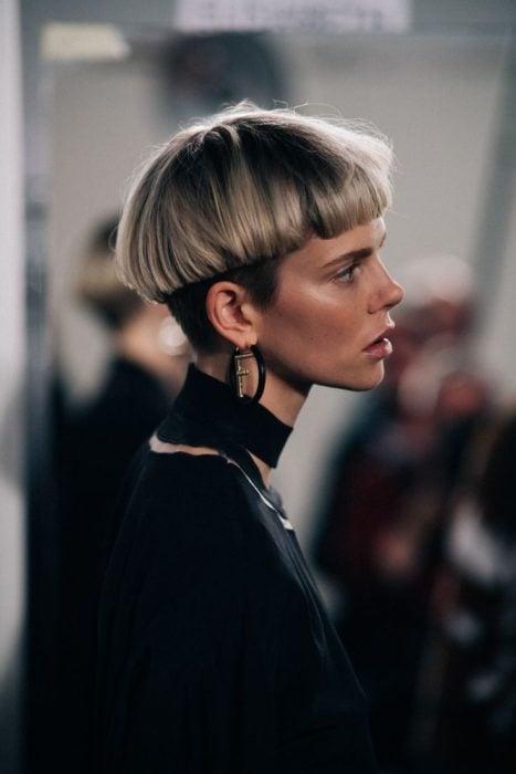 Modelo de cabello rubio matizado con corte bowl vistiendo de negro