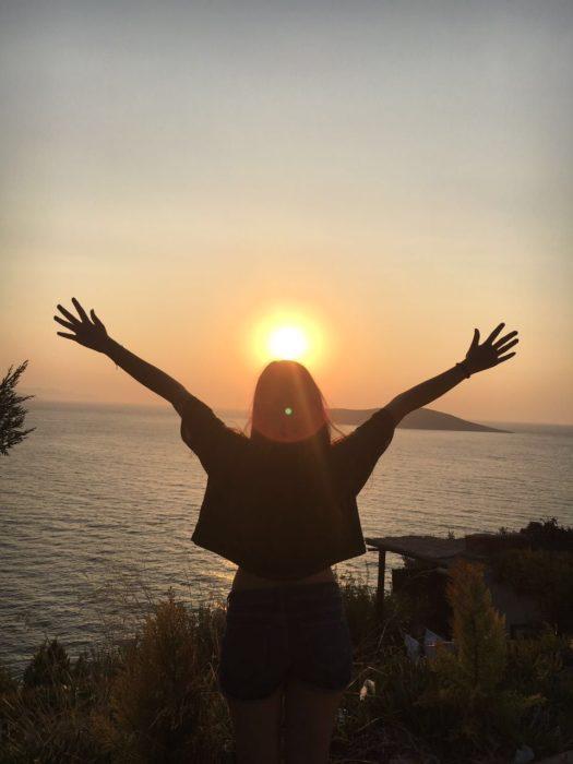 Chica con los brazos abiertos, en atardecer en la playa