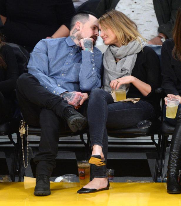 Cameron Diaz y Benji Madden sentados mirándose fijamente durante un partido de basketball
