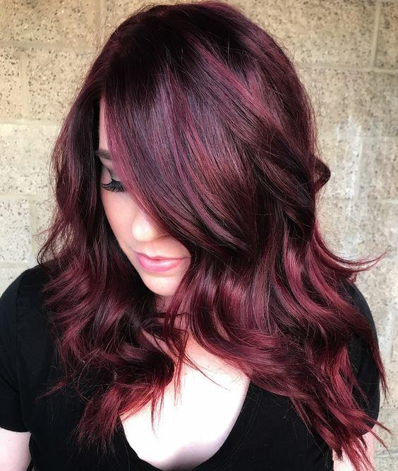 Chica con peinado en ondas ligeras teñido en cherry wine y mirando hacia abajo