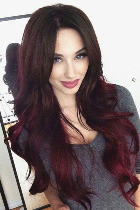 Chica recargada frente a un espejo mostrando su cabellera larga en tono cherry wine