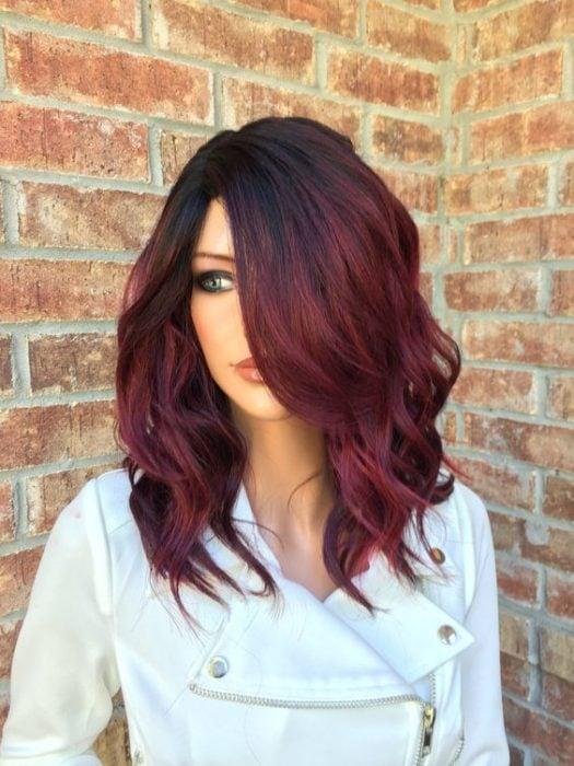 Chica con cabello midi teñido en tono cherry wine parada frente a una pared