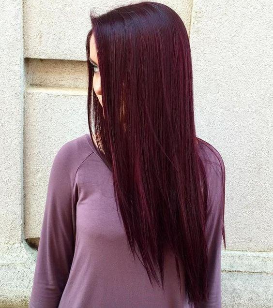 Chica de cabello extralargo volteada de perfil modelando su teñido en cherry wine
