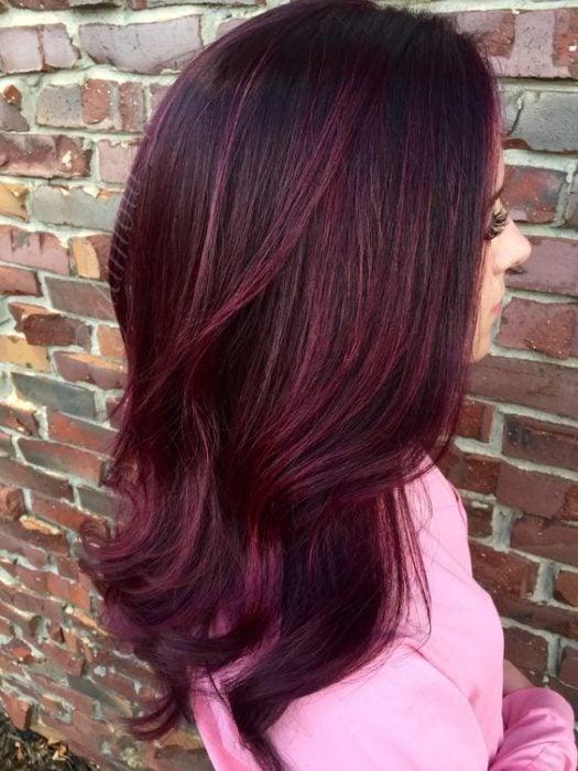 Chica girada de espaldas, modelando su cabello en ondas y teñido en cherry wine