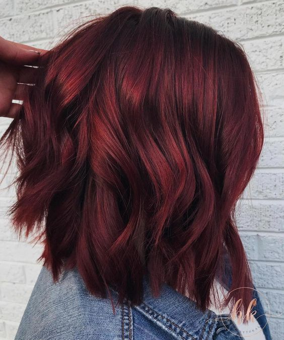 Chica de perfil mostrando su cabellera corta en tono cherry wine con ondas ligeras