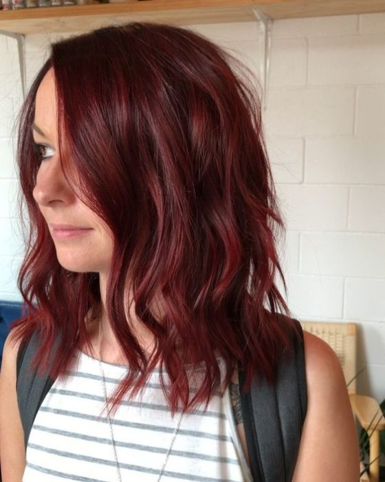 Chica sonriendo ligeramente y modelando de perfil su cabellera en tono cherry wine