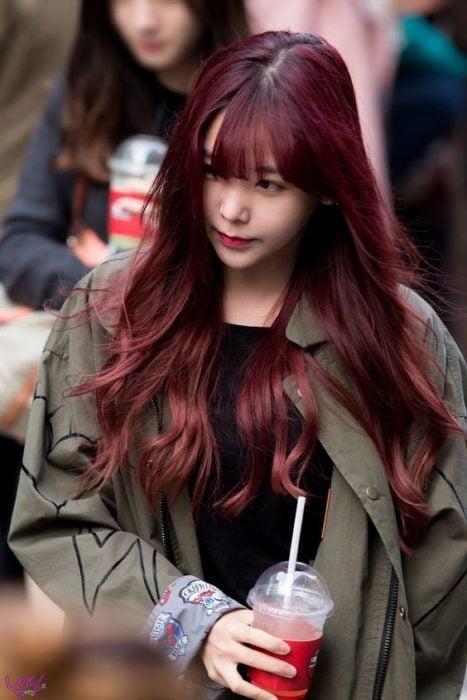 Chica con cabello largo, maninanco en la calle y mostrando su cabello en tono cherry wine