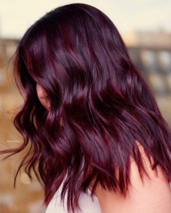 Chica de perfil mostrando su cabello con ondas en tono cherry wine y luces violeta