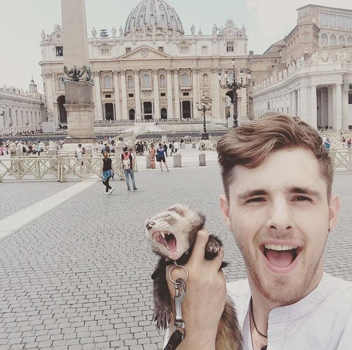 Chico sujetando a un hurón mientras están enfrente de un monumento en Europa