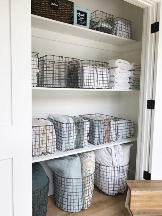 Organización en closet pequeño en conastillas de tonalidades oscuras