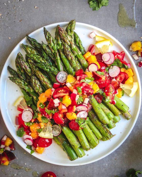 Plato de comida alcalina, esparragos con rabanos, y verduras varias, además de aceite de oliva