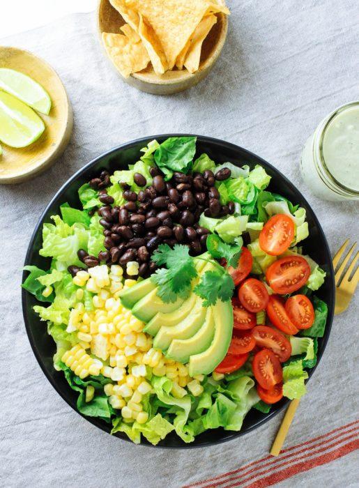 Plato de comida, ensalada con legumbres, limón, y algunos totopos