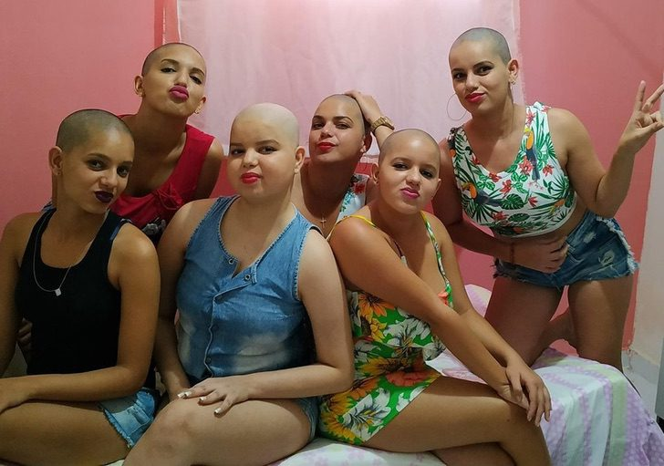 Grupo de mujeres luciendo su cabeza sin cabello apoyando a su amiga con leucemia