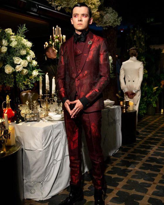 Asa Butterfield con un traje en rojo vino en un gran comedor