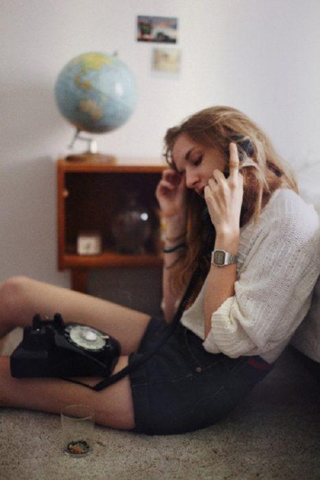 Chica llamando por teléfono fijo