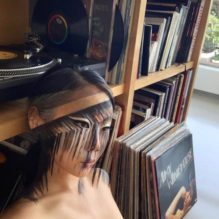 Dain Yoon, artista maquillaje, pintura reflejando librero con discos de acetato