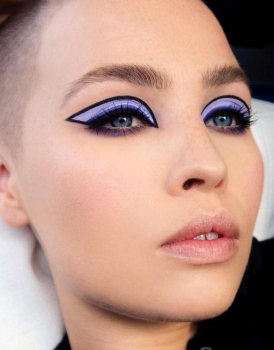 Maquillaje tendencia para el 2020;; delineado gráfico o flotante con sombra morada; mujer rapada con pecas y teeth gap