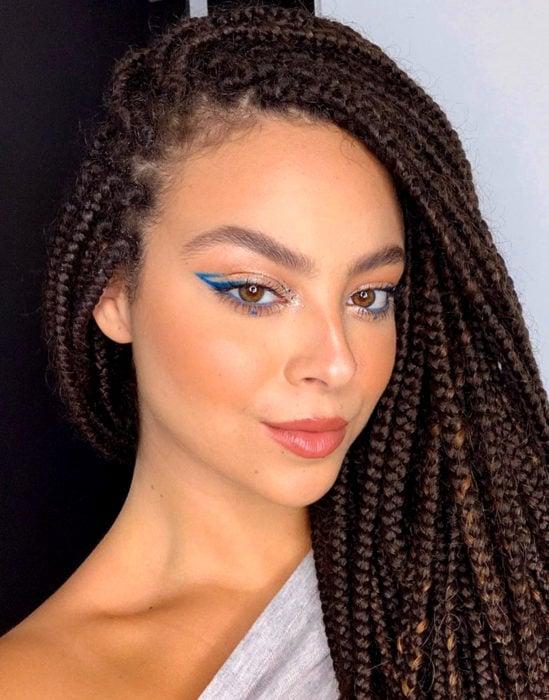 Maquillaje tendencia para el 2020;; delineado gráfico o flotante color azul; mujer afroamericana con trenzas