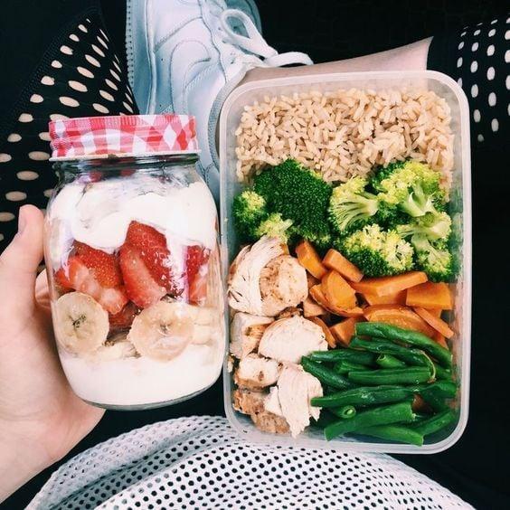 Chica sosteniendo lunch con zanahoria, brocoli, arroz y pollo