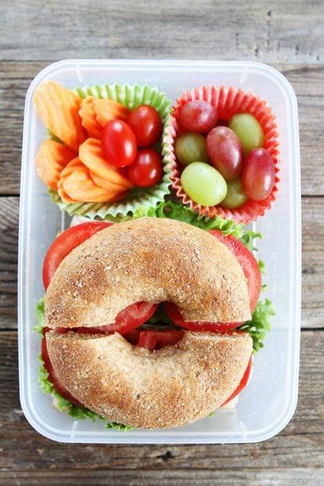 Bagle con tomate, lechuga, uvas rojas y verdes, tomate cherry y papas fritas