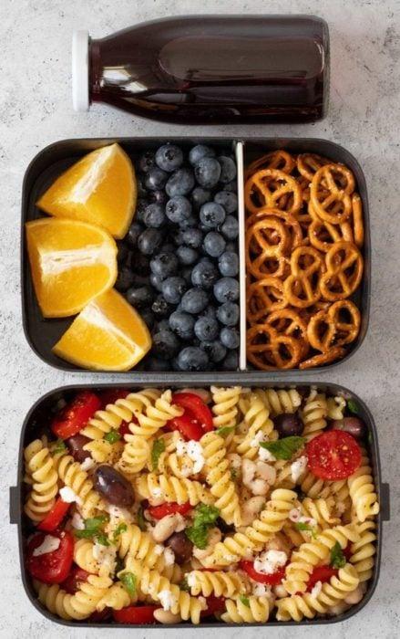 Comida de pasta con queso mozzarella, tomate cherry, moras, naranja y galletas