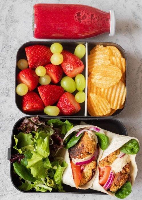 Lunch con burrito de albaca, pollo, tomate, lechuga morada, fresas, uvas verdes y papas fritas