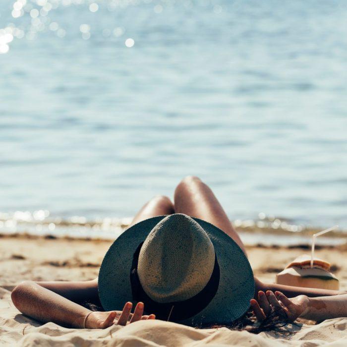 Mujer relajada en la playa, usando un sombrero para el sol y tomando agua de coco
