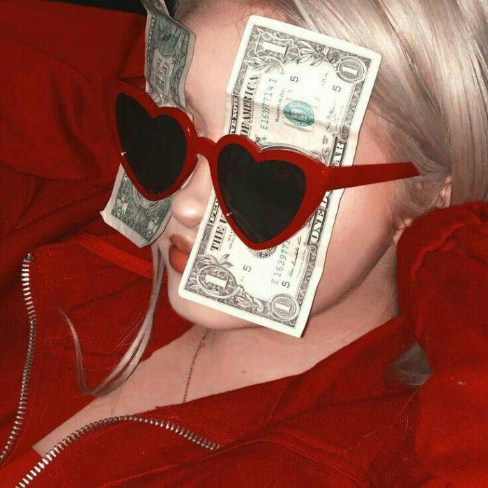 Chica con dólares en las gafas