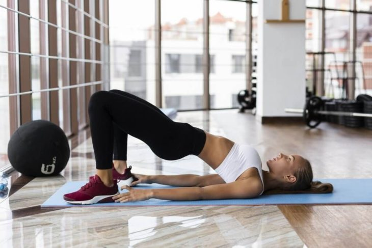 Chica realizando ejercicio 'el puente' sobre tapete de yoga en gimnasio