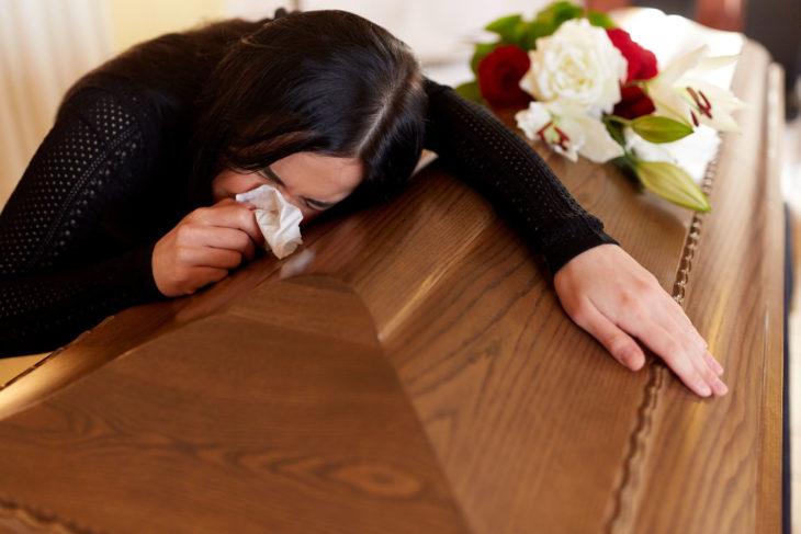Mujer asiática llorando sobre un ataud