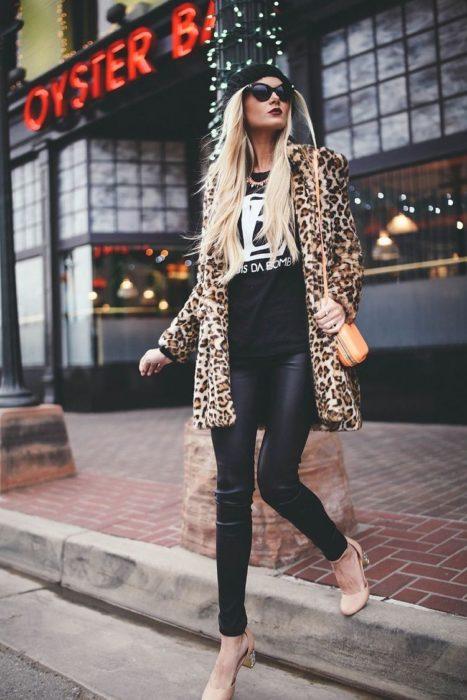Modelo con outfit de abrigo de estampado animal print, leggins negros, y accesorios
